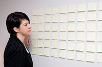 Young woman next to wall of sticky paper notes
