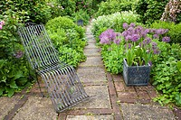Relaxing area surrounded with spring borders and decorative container planted with bulbs, Kent England.