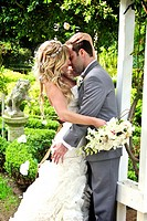 beautiful garden with bride & groom passionately embracing after the wedding