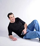Man on the floor of studio with a big smile and looking towards the camera.White background.