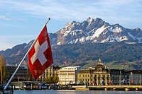 Swiss National Flag in Lucerne in Central Switzerland with the mountain range of Mt.Pilatus in the background