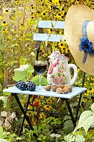 Summer arrangements in the garden includes blue painted chair, glass of domestic Slovenian vine, grapes, straw hat, walnuts and pitcher.