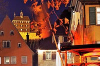 castle and medieval banners at night, esslingen, night foreshortening of illuminated castle and banners of stalls in medieval Christmas market held ev...