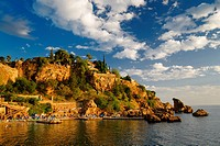 Cliffside resort and beach on Turkish Riviera at Antalya Kaleici Harbour Turkey at sunset