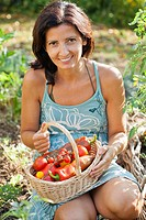 Woman with basket filled with freshly harvested vegetables.