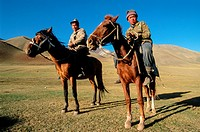 Two Kyrgyz herders riding horses, Kyrgyzstan, Central Asia.