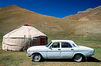 Old Russian car next to a yurt, Tash Rabat, Kyrgyzstan, Central Asia.