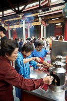 Temple functionaries help worshippers and visitors with incense and ceremonies at the Hsingtian Temple.