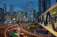 people and traffic pass through Central Hong Kong construction zone at dusk.