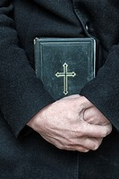 Priest holds the holy bible