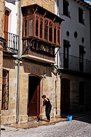 House and traditional balcony in òbeda, woman cleaning the entrance on a sunny day, òbeda, JaŽn province, Andalusia, Spain.