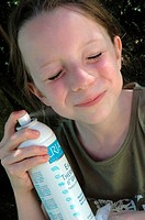 8 years old girl refreshing her face with a water spray during a summer heat.