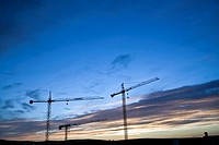 Several cranes abandoned at the sunset in a construction of buildings, Spain.