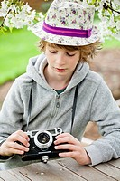 Boy playing with an old camera.