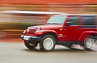 Panning photograph of a Jeep /SUV in motion, showing a blurred background created by camera movement or a panning technique.