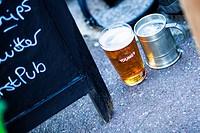 Old and new jug/mug beer pints next to a pub sign, London, UK