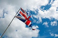 A tattered British Union flag is seen flying against a blue sky.