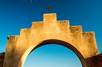 An iconinc adobe arhway and crucifix at a Spanish mission in Arizona.