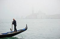 A Gondola passing by in front of San Giorgio Maggiore In Venice covered in thick fog, Italy.
