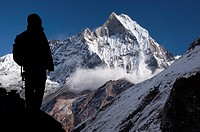 Avalanche on the holy Machapuchare mountain viewed from Annapurna Base Camp, silhouette of a trekker in the foreground. Nepal, Gandaki, Annapurna, Ann...
