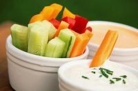 Vegetable sticks and dips in bowls.