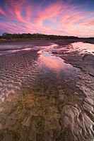 A small path of water in a partially dry lake bed in southern Texas under a stunning sunset sky.