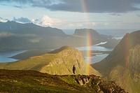 Person stands under rainbow near summit of Ryten, Lofoten Islands, Norway.