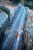 Runaway overhead view of child with arms outstretched abandoned road playing, Berrocal, Huelva, Andalucia, Spain