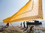 Sari being dried in front of a river in Varanasi, Uttar Pradesh, India.