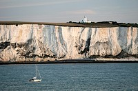 Yacht passing along the White cliffs of Dover in the English Channel east of Dover below South Foreland lighthouse. Dawn light.