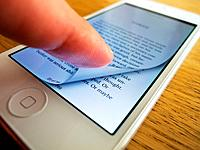 Detail of iPhone 5 smart phone screen showing iBooks e-book reader with page turning.