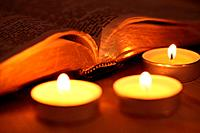 Close-up of candles and open Bible.