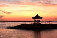 A three people in a Balinese Pagoda on the beach at Sanur. Taken at dawn. Bali, Indonesia.
