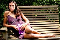 Portrait of a 27 year old brunette woman in a summer dress sitting on a bench looking at the camera in an outdoor setting holding a bowl of grapes.