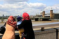 Women with headkerchief looking at River Thames with Cannon Street Railway Bridge and the dome of St Paul's Cathedral in the background. London. Engla...