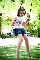 young girl swinging in beautiful greenery