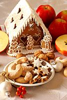Gingerbread house, christmas cookies and apples.