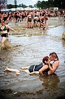 A couple kissing in a mud pool of the Przystanek Woodstock music festival, Kostrzyn, Poland.