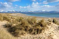 Looking across to the Snow covered Mountains of the Snowdodia National Park from beach on Llanddwyn Bay Isle of Agglesey North Wales.