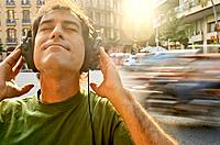 Man listening to music with headphones on a street.