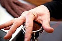 Person making fresh coffee with expresso machine.