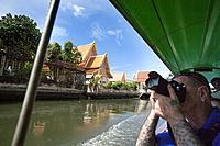 A tourist photographs temples from a longboat on one of Bangkoks many canals, Thailand.