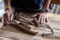 Craftsmans hands with a minature traditional Thai sampan made from teak wood, Bangkok Thailand.