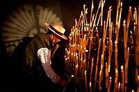 A man, wearing a Spanish hat, lights candles at the Votive Room of the shrine of the Virgin of Rocio, in Almonte, Donana National Park, Huelva provinc...