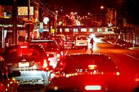 Sillouette of a pedestrain crossing road through traffic congestion at railway crossing, evening peak hour, Melbourne Australia