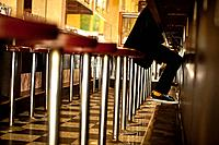 A young man wearing sneakers sits on a bar stool in cafe, central Melbourne, Australia
