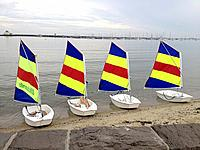 Four small sail boats with multi coloured sails sitting on St Kilda beach, Melbourne Australia
