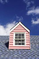 Image of a pink dormer on a shingled roof with a blue sky in the background.