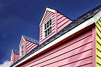 Image of three pink dormers on a house with a shingled roof against a blue sky