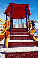 Playground equipment in winter, with snow on the steps up to the slide is empty on a clear day.